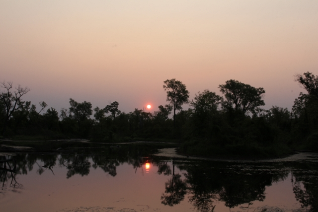 Sunrise with reflections over an old strip pit from coal mining days long ago. A swampy area now